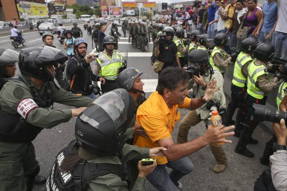 Efectivos de la Guardia Nacional Bolivariana (GNB) forcejean con un manifestante el martes 7 de junio del 2016, en Caracas. CRISTIAN HERNÁNDEZ EFE